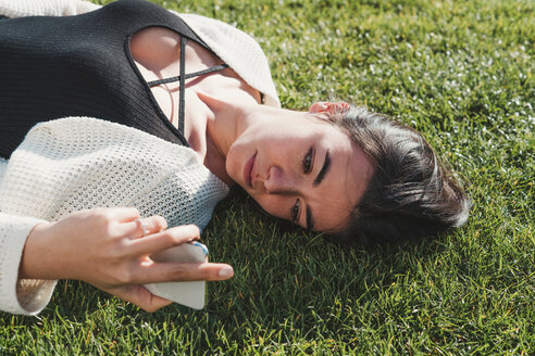 Woman lying down, using smartphone on grass - CUF50628