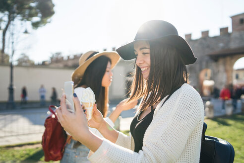 Woman taking selfie with ice cream cone, Pisa, Toscana, Italy - CUF50643