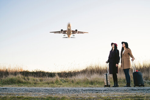 Friends waiting with wheeled luggage on roadside, airplane flying above - CUF50655
