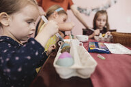 Girls painting Easter eggs on table at home - KMKF00931