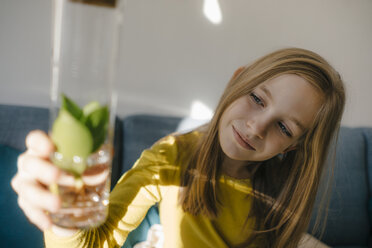 Girl at home looking at plant in a glass - KNSF05827