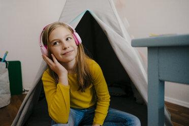 Smiling girl wearing headphones at home - KNSF05836