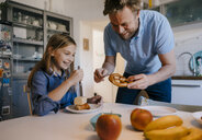 Happy father and daughter at home having fun at breakfast table - KNSF05848