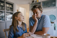 Daughter talking to father in kitchen at home - KNSF05851