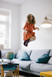 Carefree girl jumping on couch at home - KNSF05866