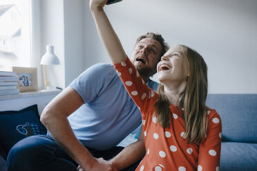 Happy father and daughter taking a selfie at home - KNSF05872
