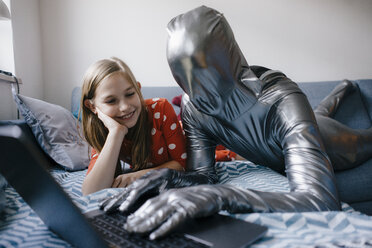 Man in morphsuit and girl lying on couch at home using laptop - KNSF05887