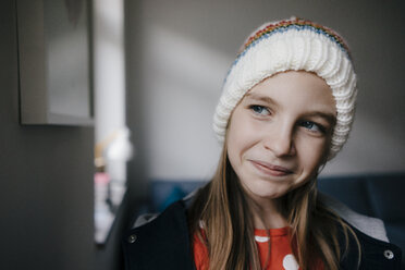 Portrait of girl wearing wooly hat at home - KNSF05890