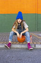 Young girl sitting on basketball - ERRF01244