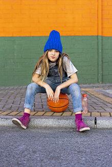 Young girl sitting on basketball - ERRF01244