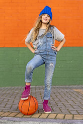 Young girl with foot on basketball - ERRF01247