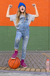 Young girl with foot on basketball - ERRF01250