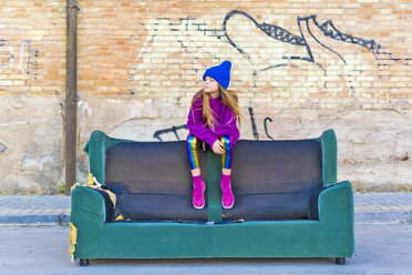 Girl wearing colorful clothing and sitting on a couch outdoors - ERRF01259