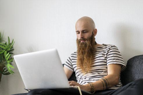 Portrait of hipster using laptop at home - AFVF02933