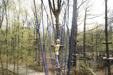 Young woman wearing yellow t-shirt and helmet in a rope course - EYAF00195