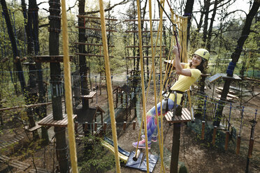 Young woman wearing yellow t-shirt and helmet in a rope course - EYAF00198