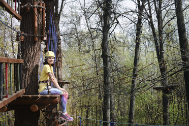 Young woman sitting on a platform in a rope course - EYAF00201
