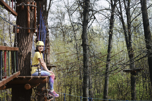 Russia, Moscow, young woman in yellow t-shirt, yellow helmet and rainbow pants sitting in rope park - EYAF00201