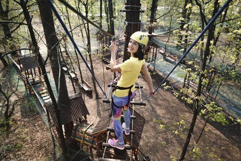 Young woman wearing yellow t-shirt and helmet in a rope course - EYAF00204
