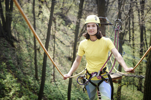 Young woman wearing yellow t-shirt and helmet in a rope course - EYAF00207