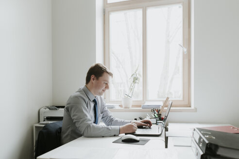 Young businessman using laptop at desk in office - AHSF00294