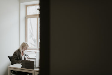 Young woman working at desk in office - AHSF00321