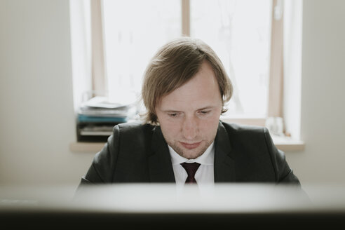 Lithuania, Kaunas, Man working at computer in office - AHSF00324