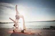 Women practising acro yoga at seaside - CUF50665
