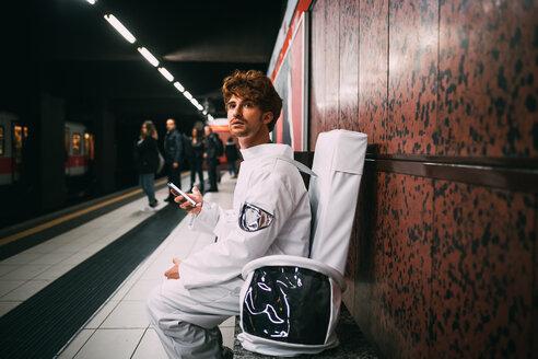 Astronaut using smartphone on train platform - CUF50674