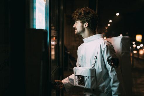 Astronaut opening door to shop at night - CUF50686