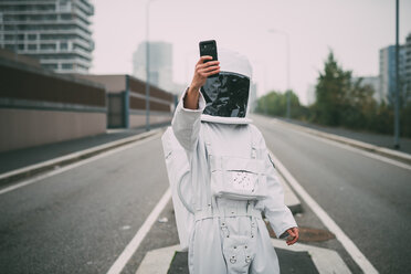 Astronaut taking selfie in middle of road - CUF50698
