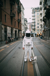 Astronaut and pet dog in middle of street - CUF50704