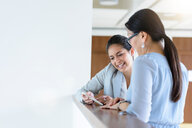 Businesswomen talking and using smartphone in office - CUF50776