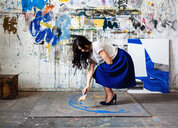 Woman painting on floor in front of wall with graffiti - CUF50779