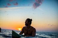 Surfer gliding in sea at sunset, Pagudpud, Ilocos Norte, Philippines - CUF50872