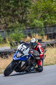 Male motorcyclist leaning sideways riding his motorbike on race track, Bangkok - CUF50956