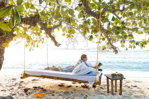 Woman reading book on swing bed in beach, Ginto island, Linapacan, Philippines - CUF51013