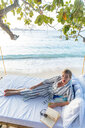 Woman reading book on swing bed in beach, Ginto island, Linapacan, Philippines - CUF51016