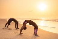 Couple practising yoga on beach - CUF51064