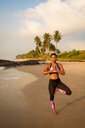 Woman practising yoga on beach - CUF51067