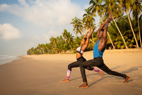 Couple practising yoga on beach - CUF51070