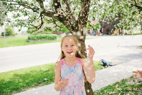 Girl throwing blossom on suburban street, portrait - ISF21301