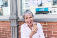 Senior woman sitting on sidewalk with chocolate ice cream cone, portrait - ISF21310