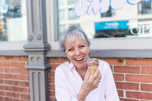 Senior woman sitting on sidewalk with chocolate ice cream cone, portrait - ISF21310