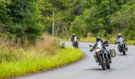 Male friends riding ADV motorcycles on rural road in Cambodia - ISF21409