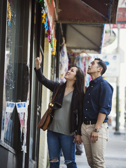 Curious Chinese couple window shopping in city - BLEF03063