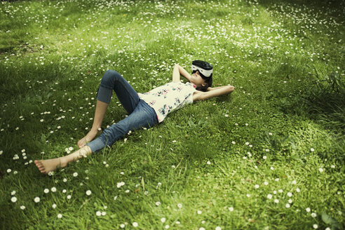 Mixed Race girl laying in grass wearing virtual reality goggles - BLEF03099
