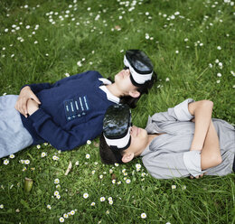 Mixed Race brother and sister laying in grass wearing virtual reality goggles - BLEF03105