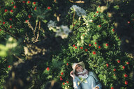 Smiling Caucasian woman laying in flowers - BLEF03120