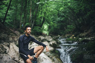 Caucasian man sitting on rocks near forest stream - BLEF03135